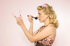 Pin-up gir doing make-up Stock Image