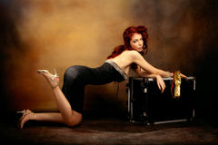 Pin up girl. Beautiful red hair woman in sexy dress leaned on trunk, studio shot Royalty Free Stock Photo