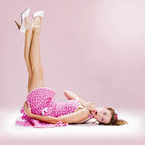 Pin-up girl. A beautiful inocent pin-up girl over a pink background Stock Image