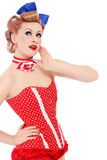 Pin-up girl. Beautiful young sexy pin-up promo girl in polka dot corset looking upwards with curious expression, on white background Royalty Free Stock Image