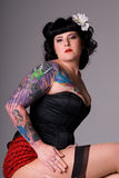 Pin-up girl. Portrait of a woman with Pin-up style hair and make-up, wearing a black satin corset. She has lots of colorful tattoos royalty free stock photography
