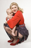 Pin-up girl with baby Stock Images