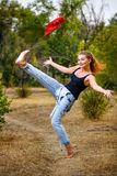 Pin-up girl. Beautiful pin-up girl barefoot in jeans overalls throws a red bandanna stock photo