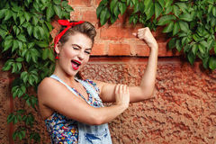 Pin-up girl. Beautiful pin-up girl in denim overalls and a red bandana  winks and demanstriruet bicep Stock Images