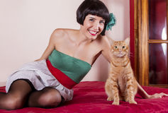 Pin-up girl in bed. View of a pin-up girl happy with short hair in bed with a cute cat royalty free stock images