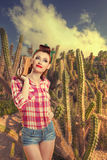 Pin-up girl in cacti. retro style. Cacti growing in a picturesque park near the sea royalty free stock photo