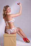 Pin up girl with cherry. Pin up girl in swimsuit and red shoes holding cherry Royalty Free Stock Photo
