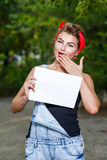 Pin-up girl and copyspace. Beautiful pin-up girl in denim overalls and a red bandana holding copyspace Stock Photography