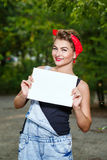 Pin-up girl and copyspace. Beautiful pin-up girl in denim overalls and a red bandana holding copyspace Stock Photos