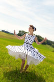 Pin up Girl is dancing and twisting on the meadow. Pin up or rockabilly Girl with rock n roll outfit is dancing and twisting on the meadow Stock Photography