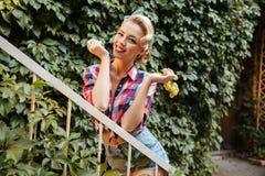 Pin-up-Girl, das Weintraube hält und isst lizenzfreie stockfotos