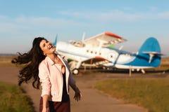 Pin-up-Girl in der Lederjacke nahe dem alten Flugzeug Mode-Lebensstil, Porträt stockfotos