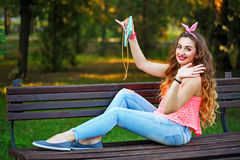 Pin Up Girl doing selfie on the phone in park. royalty free stock photos