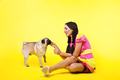 Pin-up girl in doll dress feed a dog with cheese Royalty Free Stock Image