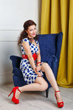 Pin-up girl in a dress and shoes sits on a chair. Stock Photos