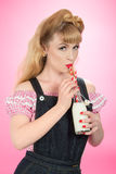 Pin Up Girl. Drinking milk from a retro swing top bottle with straws Royalty Free Stock Photos
