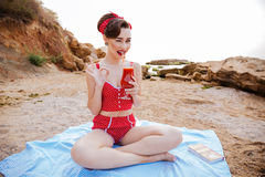Pin up girl drinking tomato juice and showing okay sign Stock Photo