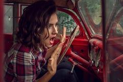 Pin-up-Girl in einem karierten Hemd wird und das Schreien erschrocken und betrachtet den Geschwindigkeitsmesser in der Kabine von stockfotografie