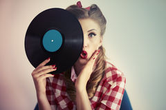 Pin-up girl. Face hidden behind the vinyl Stock Photos