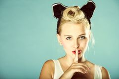 Pin up girl finger near mouth silence gesture. Portrait of a cute blonde pin up girl with a finger on her lips showing to keep silence, hush royalty free stock images