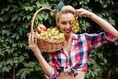 Pin-up girl with fruit basket covered eye by grape. Happy playful pin-up girl with basket of fruits covered her eye with grape in the garden Stock Photography