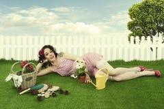 Pin up girl gardening. Pin up girl watering flower in a garden Stock Photos