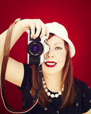 Pin up girl holding a vintage camera. Red background. Royalty Free Stock Image