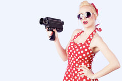 Pin-up girl. Holding vintage 8mm camera Royalty Free Stock Photo