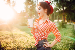 Pin up girl holds cardboard cup with a straw stock photography