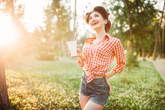 Pin up girl holds cardboard cup with a straw royalty free stock image