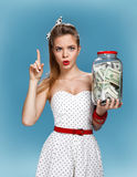 Pin-up girl with a jar of money having an idea how to spend them. Shopping concept Royalty Free Stock Photo