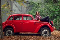 Pin-up girl in jeans and a plaid shirt is posing on a russian red retro car.