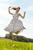 Pin up Girl jumping in the meadow Royalty Free Stock Images