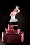 Pin-up girl jumping toy cake. Pin-up girl in a white corset and tulle skirt with a jumping toy cake Stock Photos