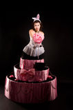 Pin-up girl jumping toy cake. Pin-up girl in a white corset and tulle skirt with a jumping toy cake Royalty Free Stock Photo
