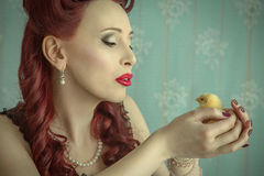 Pin-up girl kissing a chick Royalty Free Stock Photos