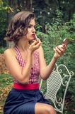 Pin-up girl with lipstick, looking in the mirror of a compact. royalty free stock photography