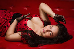 Pin-up girl lying on a red leather couch Stock Photos