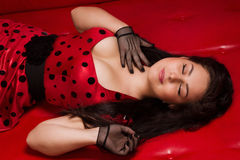 Pin-up girl lying on a red leather couch Royalty Free Stock Image