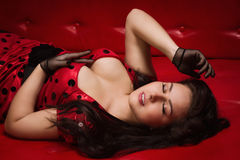 Pin-up girl lying on a red leather couch Stock Photography