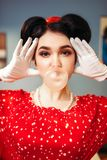 Pin up girl with make-up inflates the bubble gum. Pretty pin up girl with bright make-up inflates the bubble gum, popular american fashion 50s and 60s. Red dress Royalty Free Stock Images