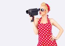 Pin-up-Girl mit dem roten Weinlesekleid, das Weinlese 8 Millimeter-Kamera hält Lizenzfreie Stockfotos