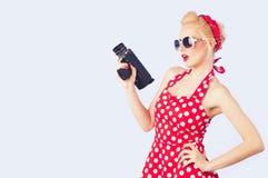 Pin-up-Girl mit dem roten Weinlesekleid, das Weinlese 8 Millimeter-Kamera hält Lizenzfreies Stockfoto