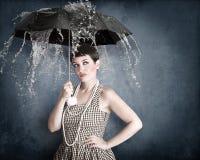 Pin-up-Girl mit Regenschirm unter Wasserspritzen Stockfotos