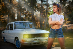 Pin-up girl near retro car on a background of forest stock image
