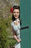 Pin up girl peeking behind a green barn  door Royalty Free Stock Images