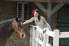 Pin up girl petting a horse on a farm Royalty Free Stock Photos