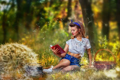 Pin-up  girl at the picnic reading a book on the background of forest and dandelions with a basket and a radio Royalty Free Stock Image