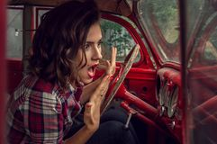 Pin-up girl in a plaid shirt is frightened and screaming, looking at the speedometer in the cabin of an old re stock photography
