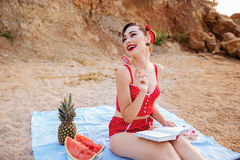 Pin up girl reading book and holding heart shaped candy Royalty Free Stock Image